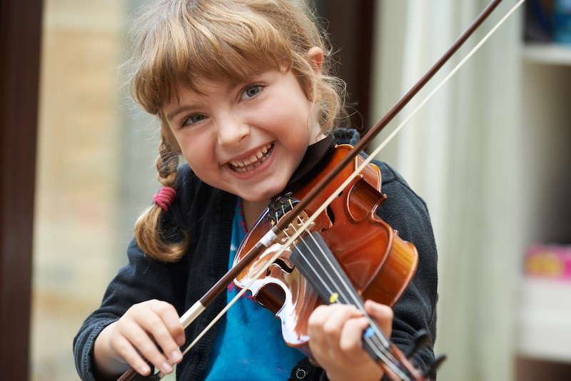 girl smiling and playing violin
